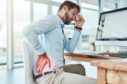 Shot of a young businessman suffering with back pain while working in an office